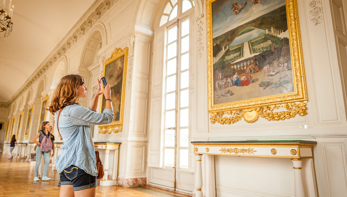 Tourist woman on summer outfit taking a picture of an oil on canvas painting on a corridor of the Palace of Versailles outside Paris, France, with other visitors.