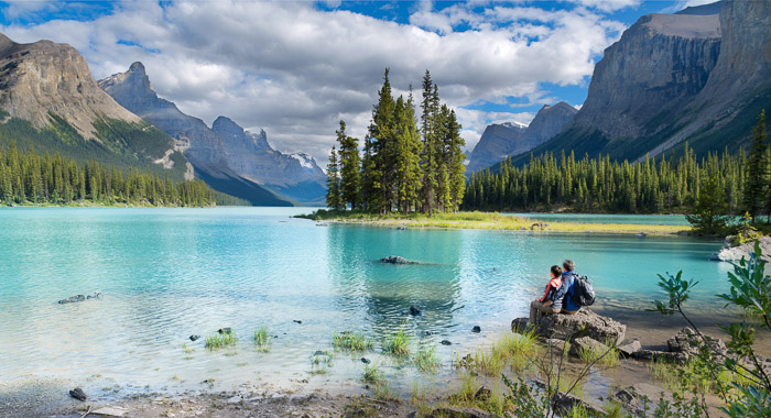 Couple by a lake with turquoise blue water surrounded by trees and the Canadian Rockies with blue sky and some clouds.