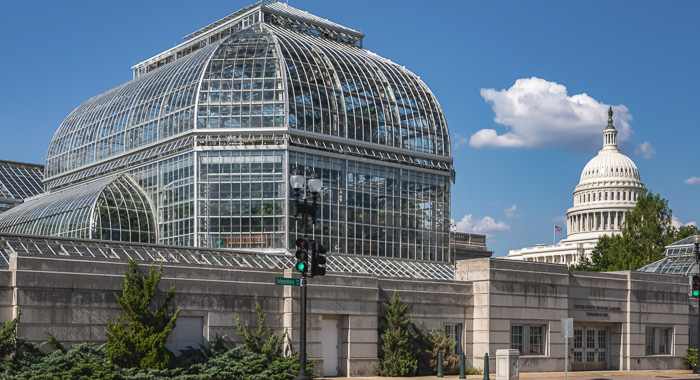 Front side of the US Botanical Gardens in Washington D.C. with see-through glass windows. In the building many species of plants from all over the world. The Capitol Building on the background.