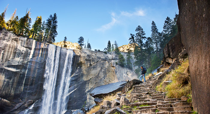 Man climbing a stone stairway looking at a waterfall falling off a stone wall with pine trees on top on a sunny day.