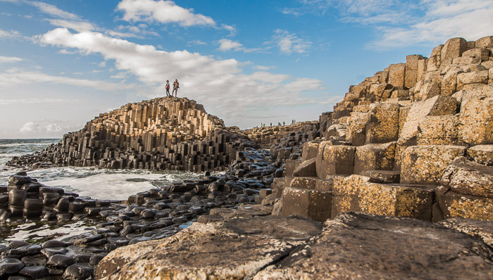 Two explorers on the top of the Giant's Causeway, a rocky formation with stones of different shapes and heights assembled in a puzzle-like way on the shore of the North Channel dividing Northern Ireland from Scotland.