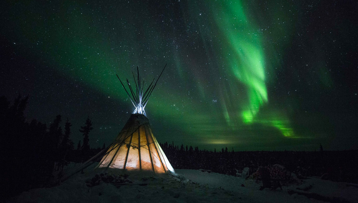 Tent set upon the snowy ground with a magnificent sight of the Northern Lights (aurora borealis) on a clear, starred night sky.