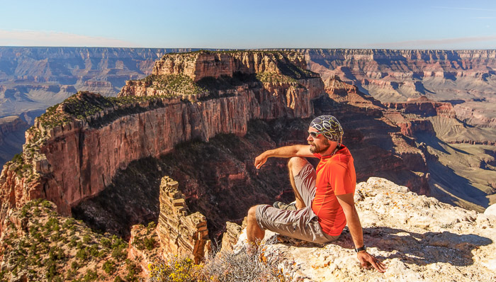 Man on hiking outfit starring at the background horizon line formed by the plateau of the Grand Canyon in Arizona, USA, on a sunny day.