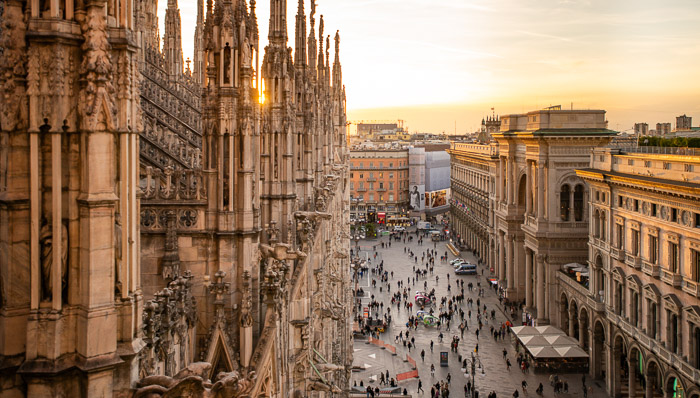 Where modern meets history. Tourists around the Milan Duomo at sunset. Grab an expresso and enjoy the scenario before it's  pizza time!