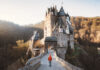 Panorama view of young explorer with backpack taking in the view at famous Eltz Castle at sunrise in fall, Rheinland-Pfalz, Germany